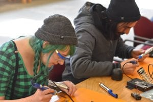 Participants on World Create Day solder a key chain flash light