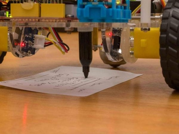 robotic pen plotter drawing on paper on a desk