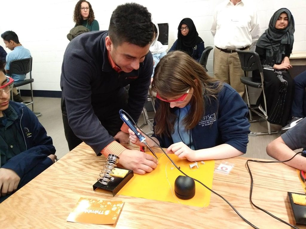 Thimble CEO helping student learn to solder