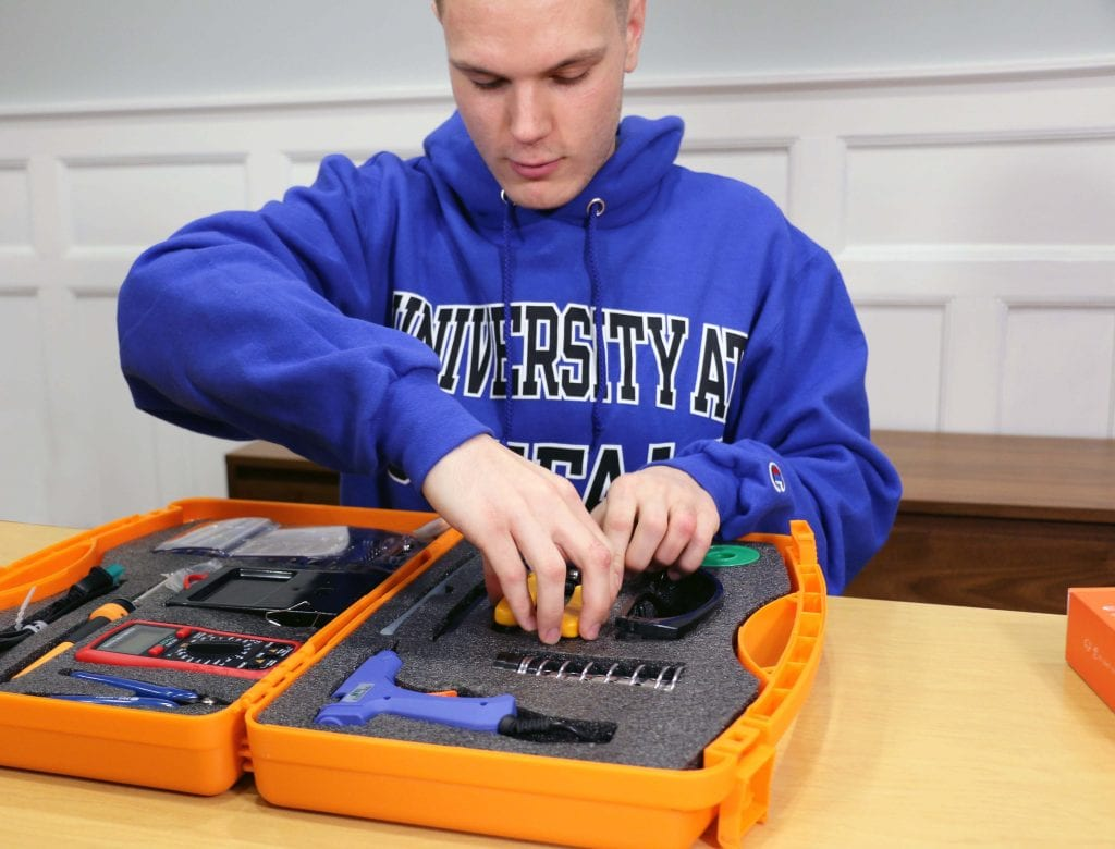 boy taking tools out of orange toolbox
