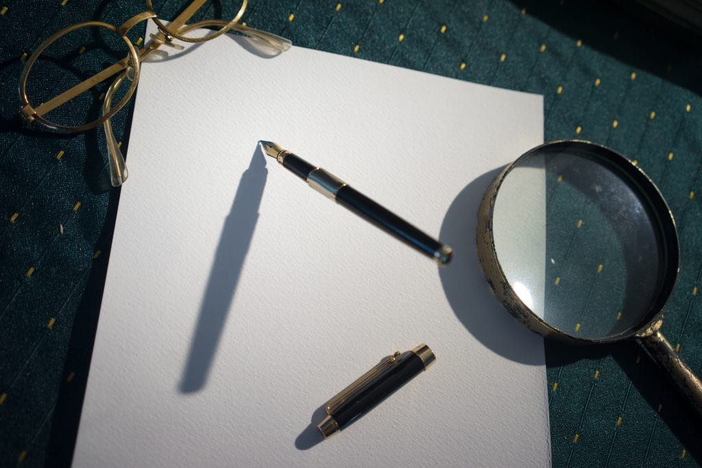 pen and magnifying glass on sheet of paper
