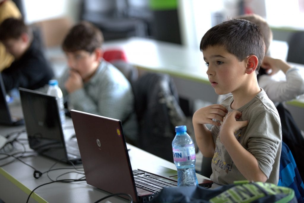 boy in computer lab surrounded by other students