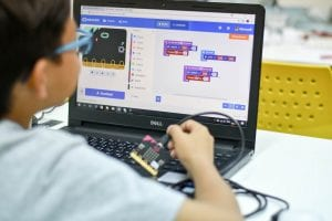 boy coding on laptop with an electronic device in hand