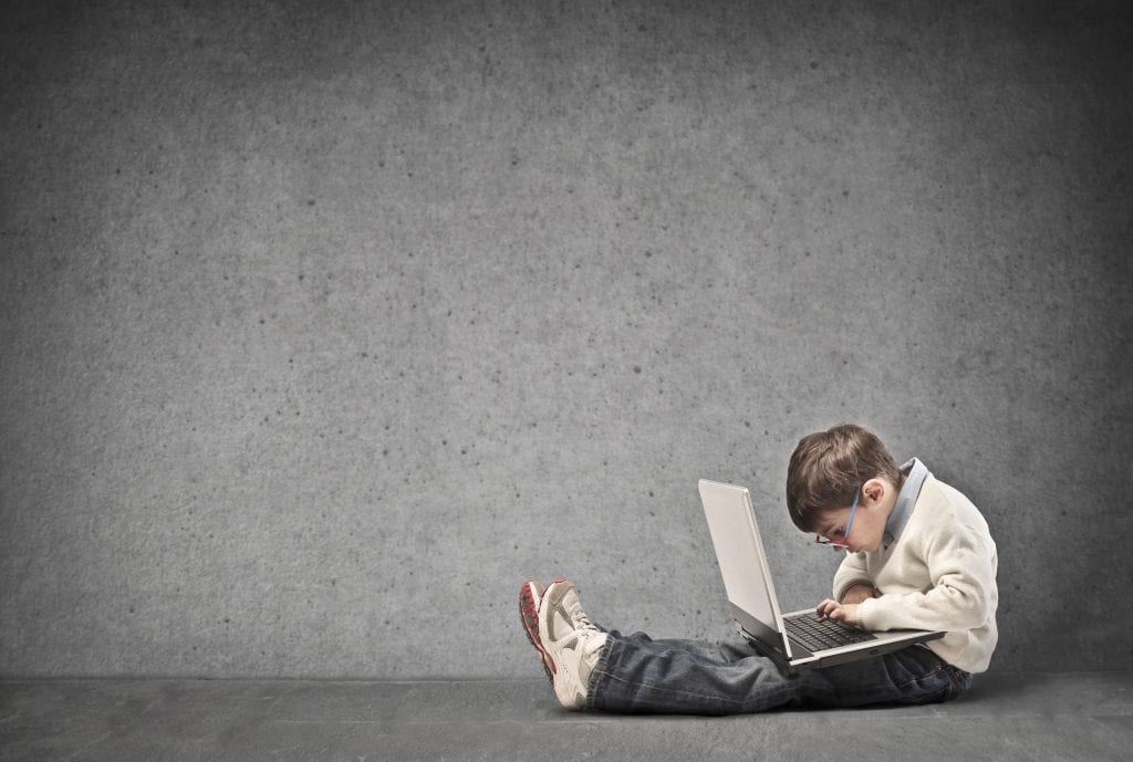 boy sitting in empty room with laptop