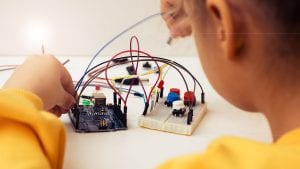 child inserts electric wires into breadboard and Arduino
