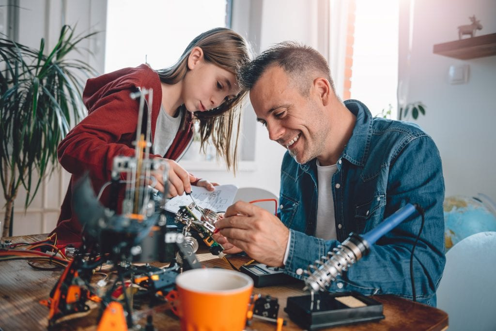 daughter and dad soldering a project together