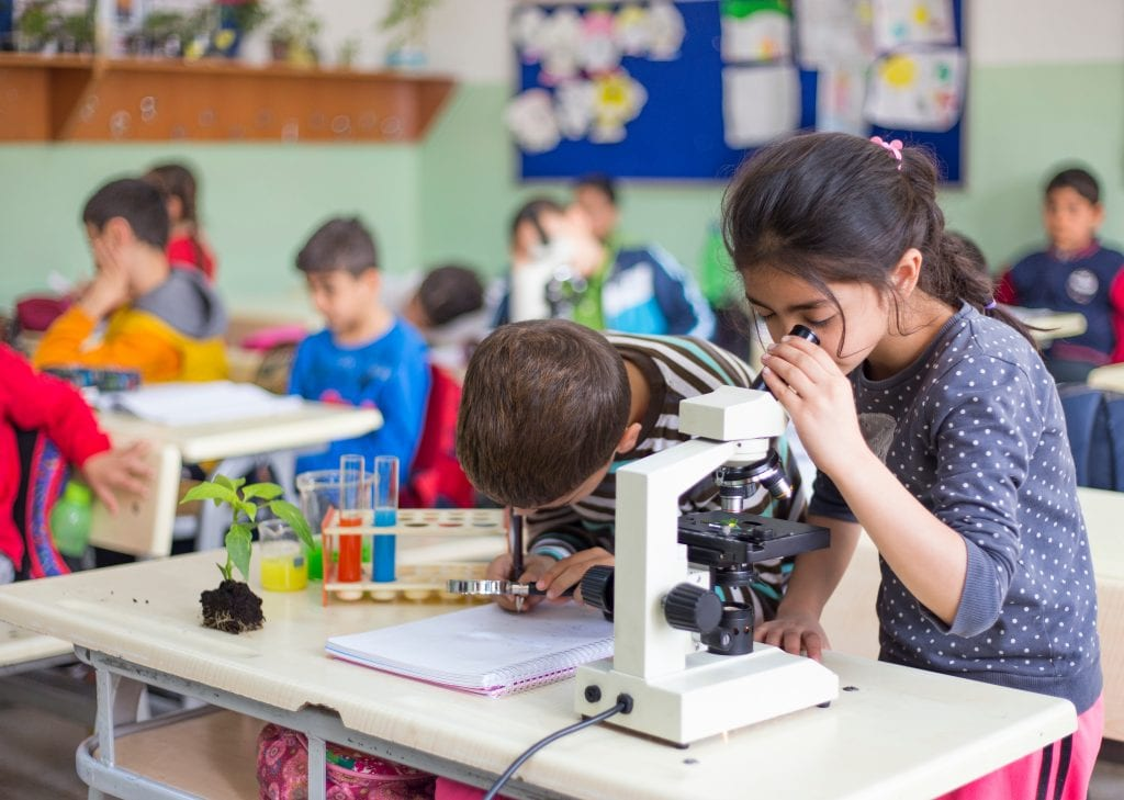 girl looking into microscope next to friend in classroom of kids