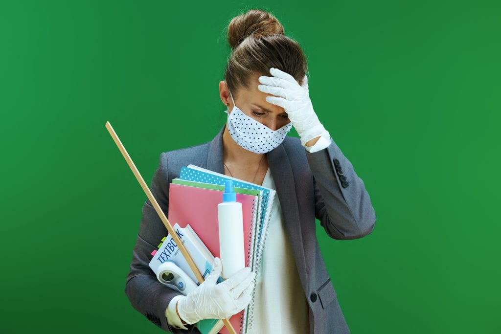 teacher holding school supplies, wearing a mask, and stressed out