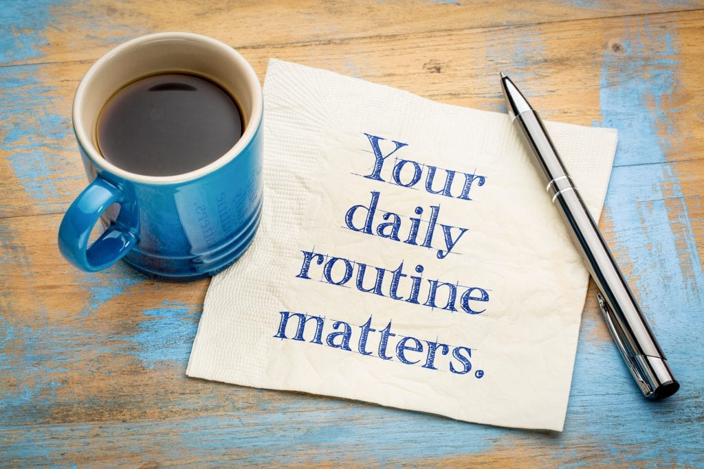 a cup of coffee, pen, and a note with a message