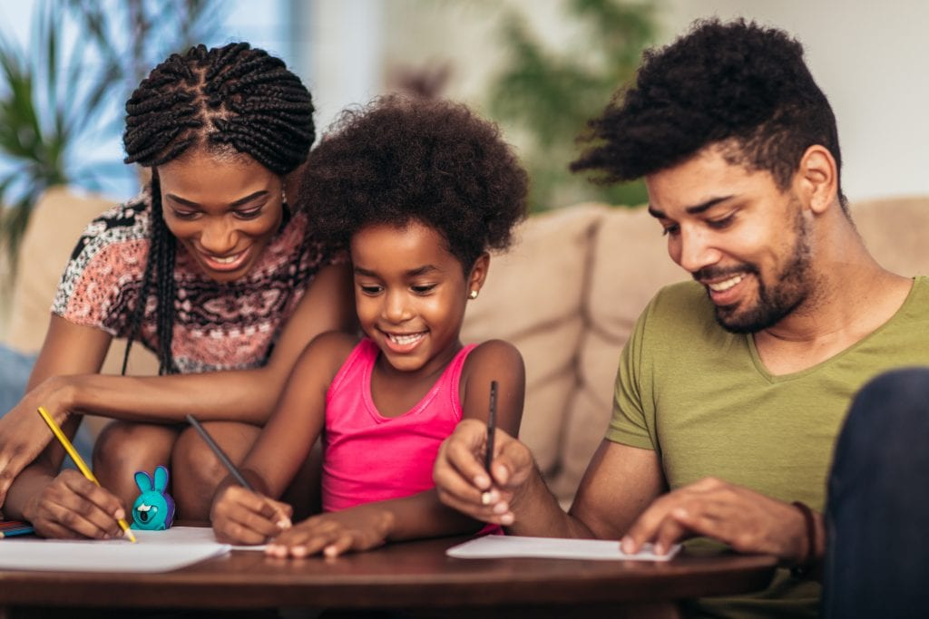 two parents helping their daughter with homework