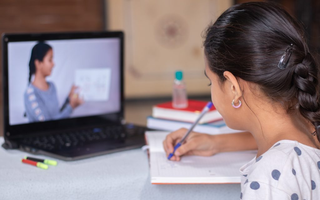 girl writing in notebook while learning on her laptop