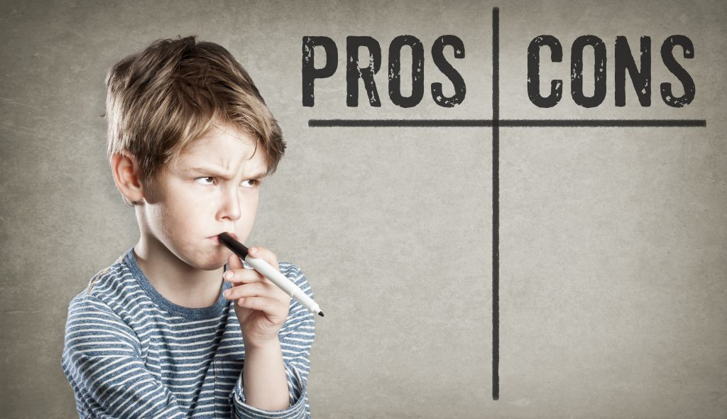 pensive boy with marker in mouth next to pros and cons chart