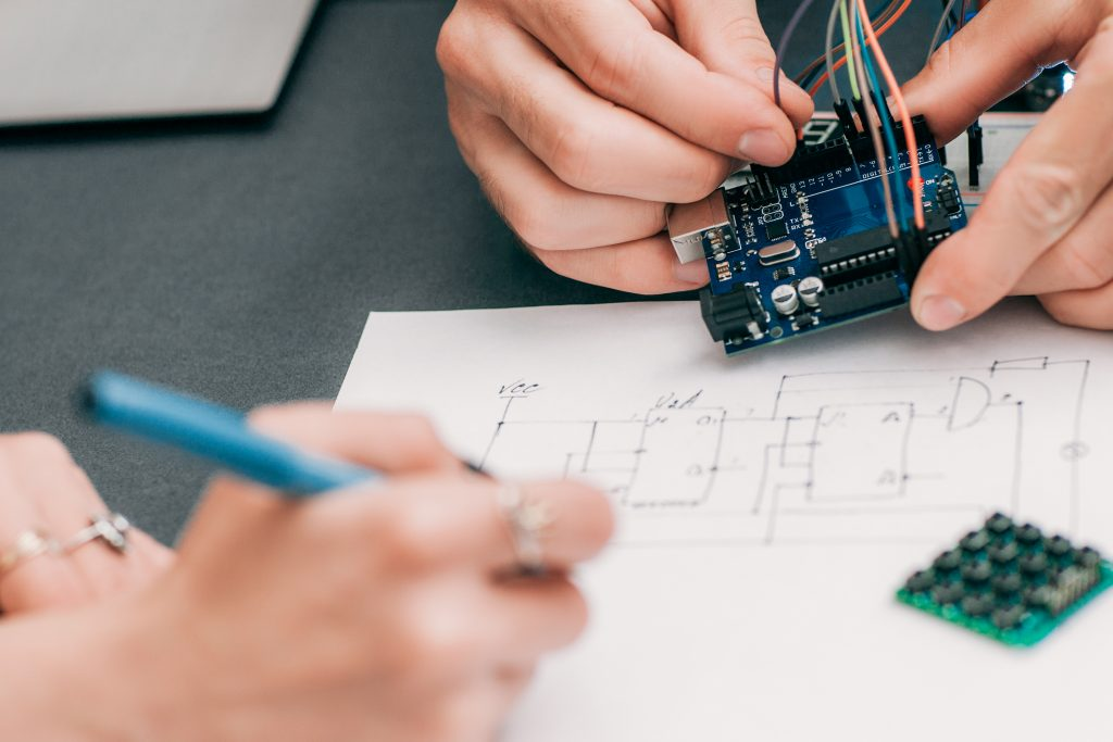 hands holding an Arduino project while another hands designs a process on paper