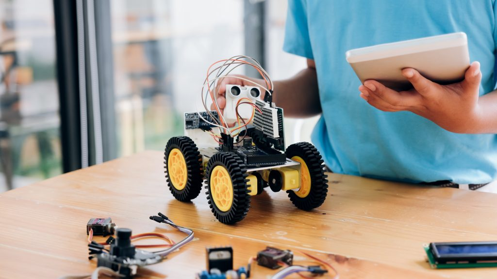 boy building a robot on desk with iPad