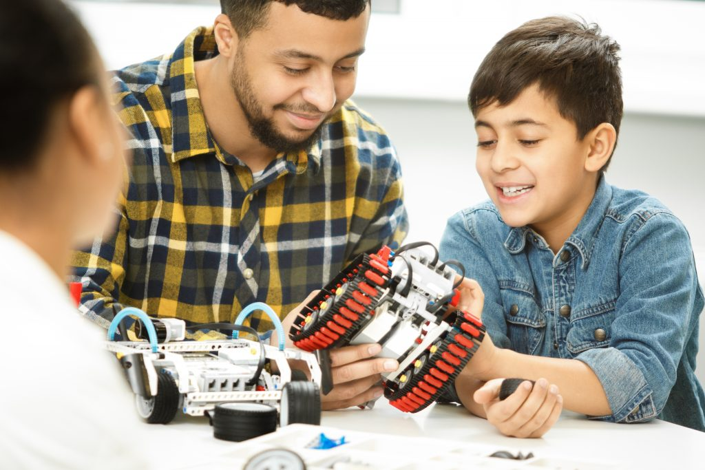 boy building robot with his mom and dad