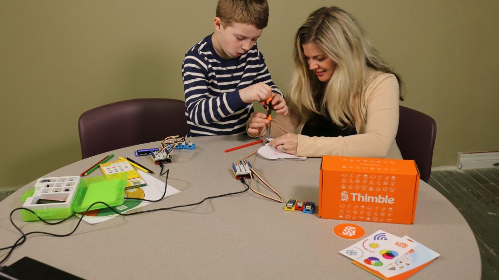 boy building STEM project with his mom at a table