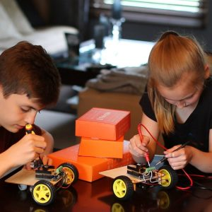 boy and girl building robots at table