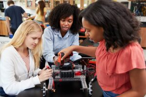 three girls building a robot in class