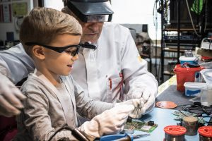 young boy handling tools with this father in a makerspace