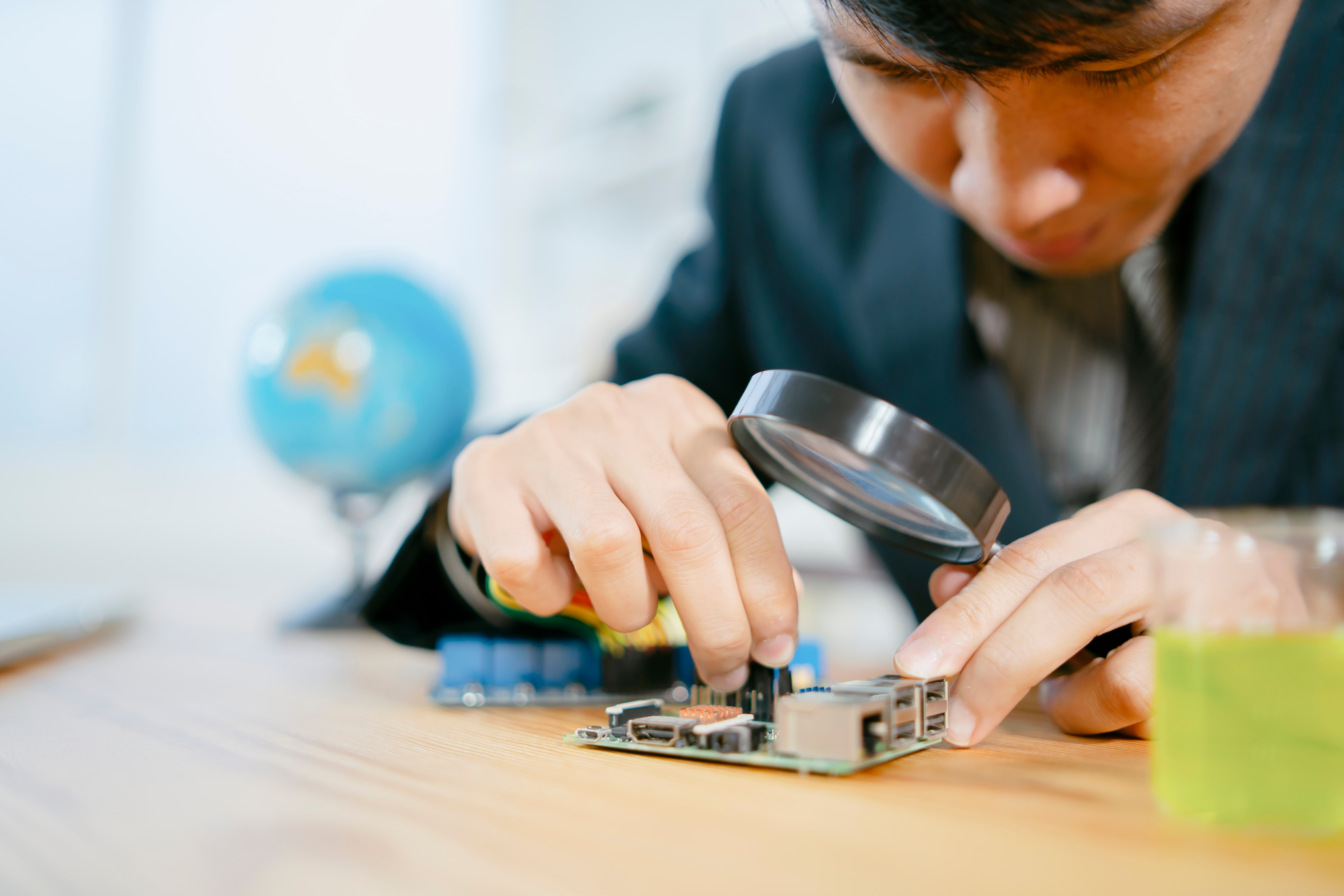 boy using a magnifying glass to examine a microcontroller