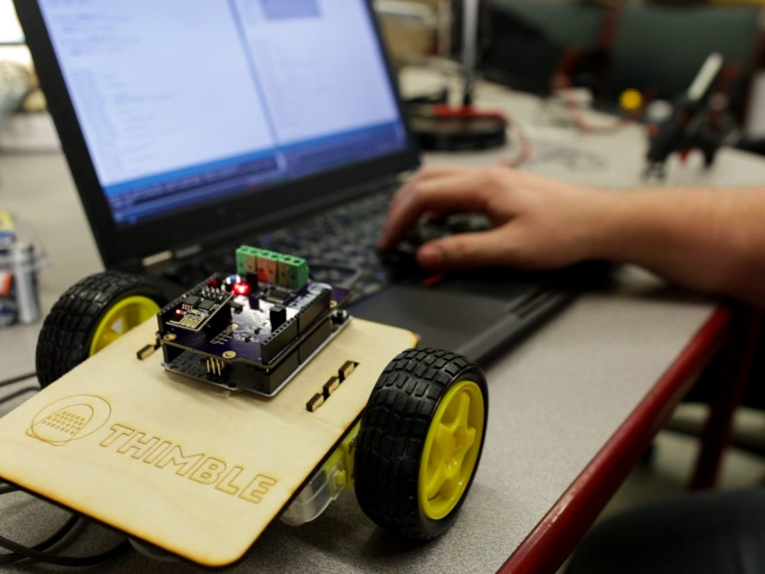 WiFi-controlled robot and hand typing on laptop