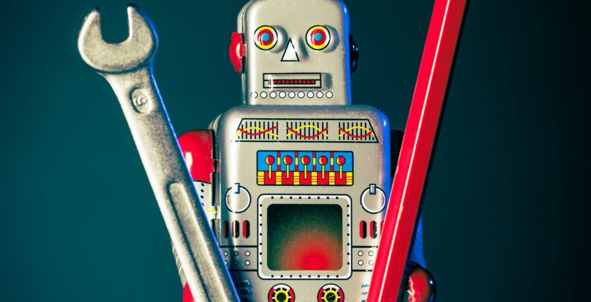 robot toy holding wrench and red pencil
